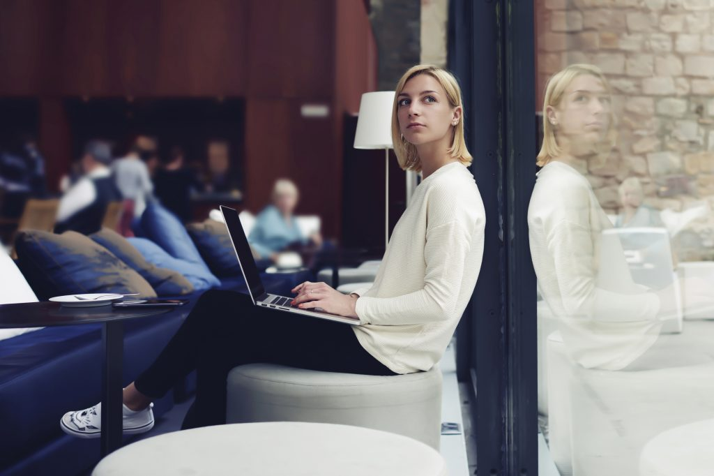 Thoughtful female person sitting in modern coffee shop interior