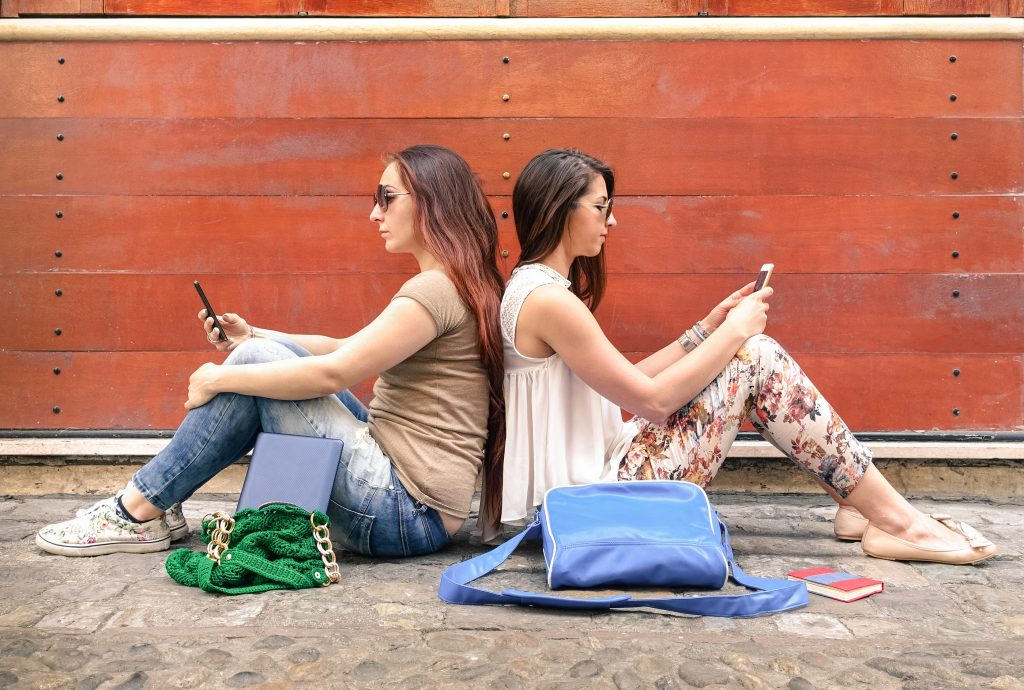 Hipster Couple Of Girlfriends In Disinterest Moment With Mobile