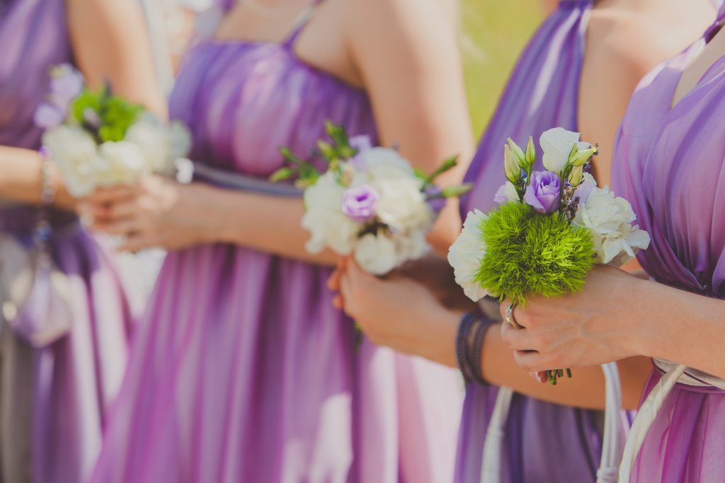 Row of bridesmaids in violet dresses with bouquets at wedding ceremony