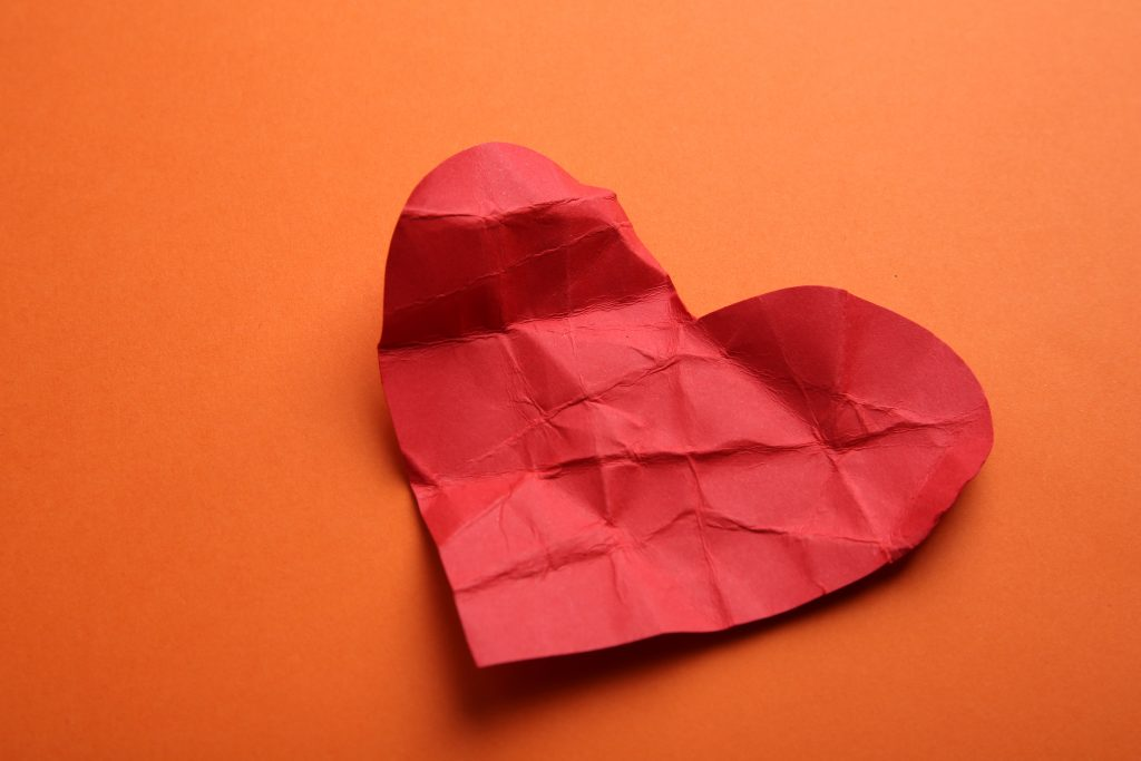 Crumpled paper heart on orange background