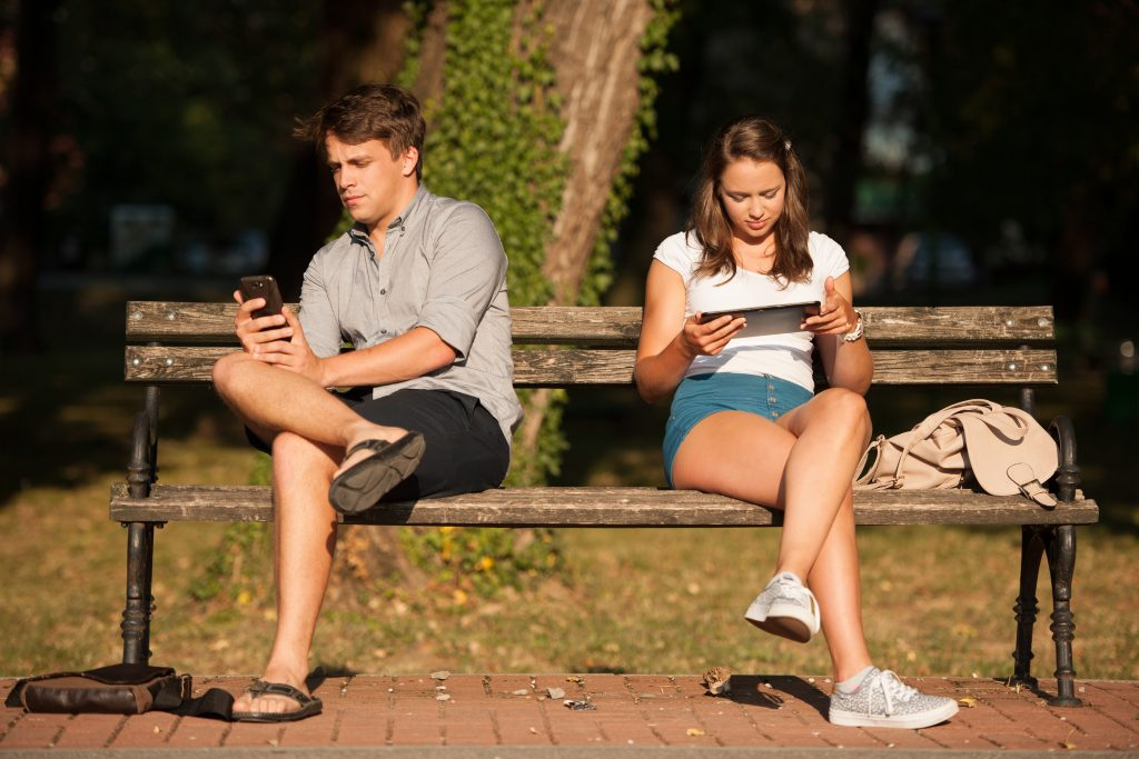 Young Couple Distracted With Communication Technology Tablet And