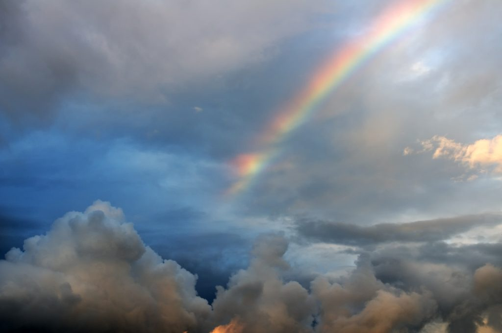 A bright rainbow in the dark cloudy sky