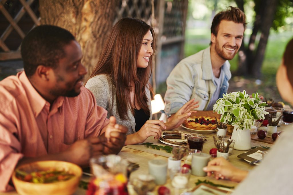 Happy young woman sitting by Thanksgiving table among her friend
