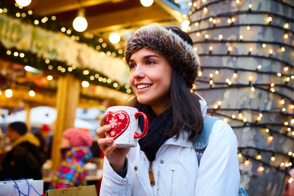 Happy young woman drinking hot drink at christmas fair, smiling,