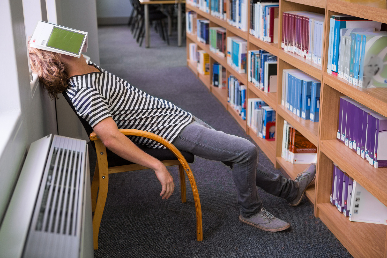 Student asleep in the library with book on his face at the unive