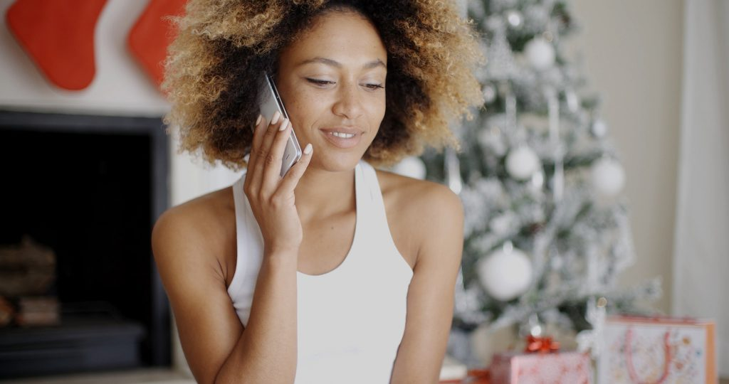 Young woman making a call at Christmas on her mobile phone to wi