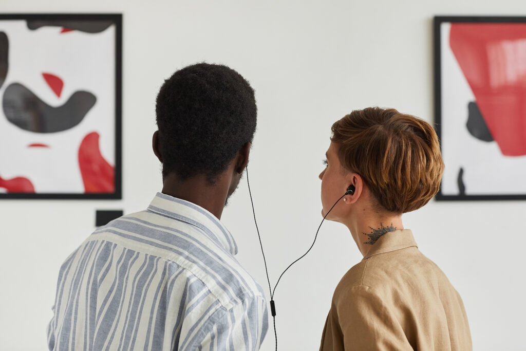 Back View Portrait Of Two Young People Looking At Paintings And sharing audio guide while exploring modern art gallery exhibition